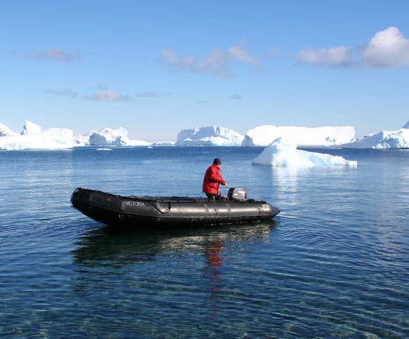Cruising in a Zodiac among icebergs in Antarctica in February